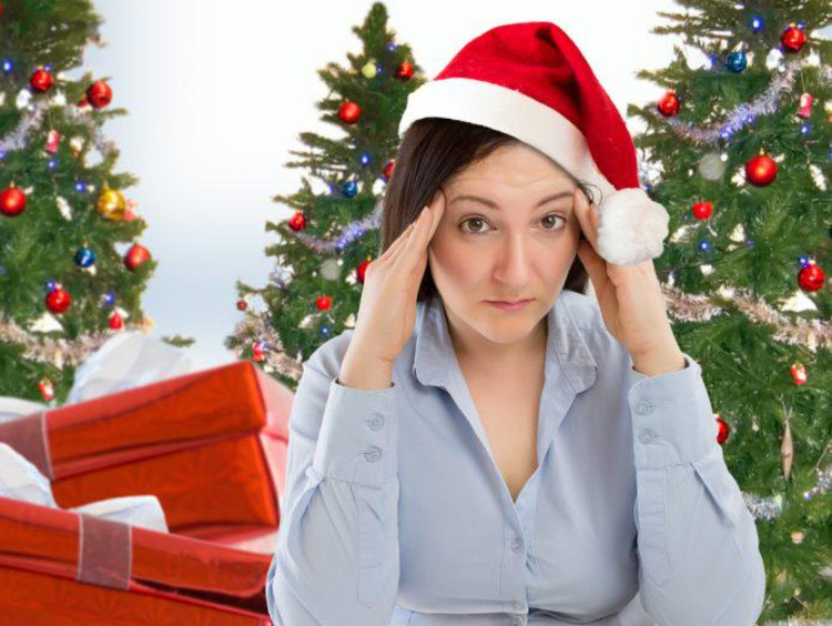 A woman in a Santa hat rubbing her temples in front of a Christmas tree