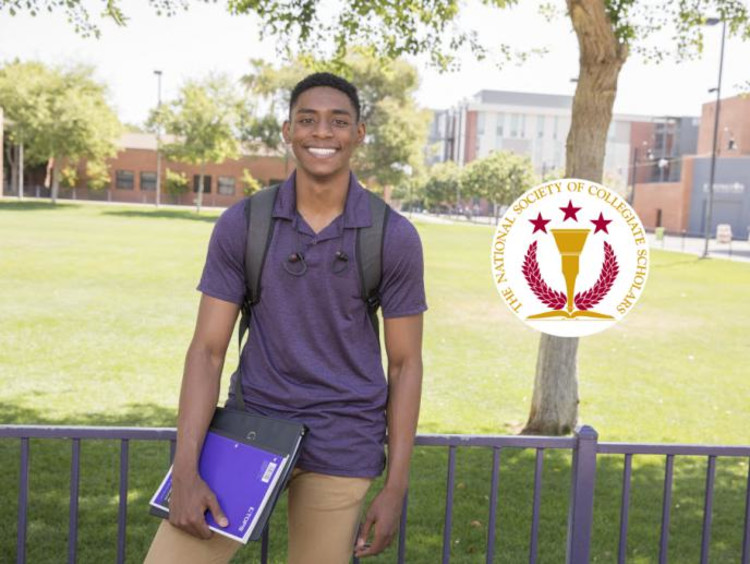 student holding notebook and wearing a backpack smiling