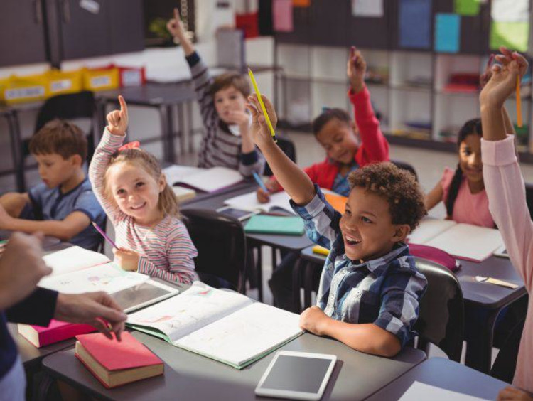 Children raise hands to answer a question in classroom setting