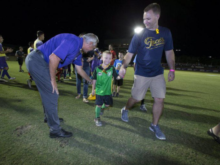 GCU's soccer team playing ball with a 10-year-old boy