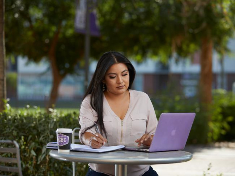 Doctoral student takes notes from laptop outdoors at GCU campus