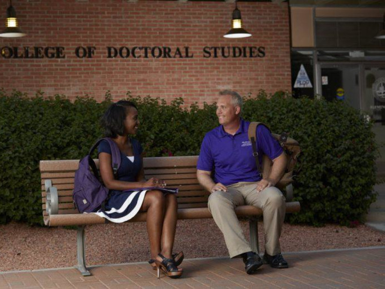 Two students sit on a bench outside the College of Doctoral Studies
