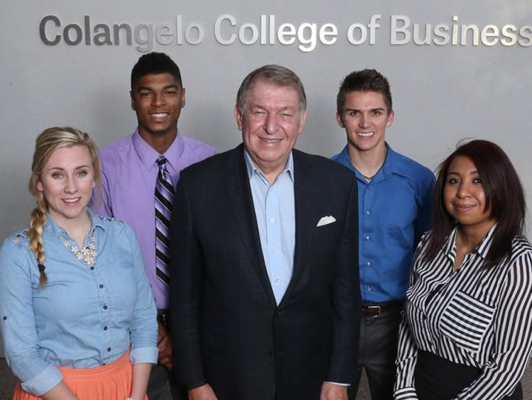 Jerry Colangelo and some business students stand in the CCOB lobby