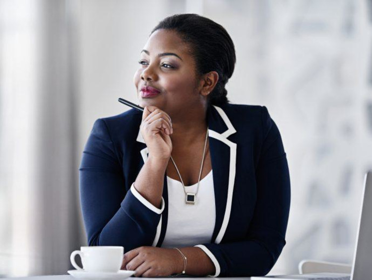 Confident African-American female looks out window daydreaming