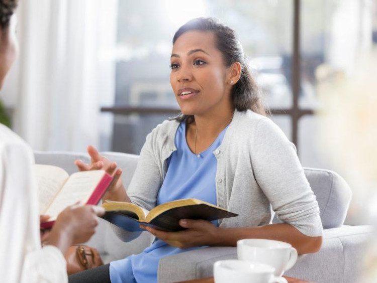Two young adults discussing the bible together