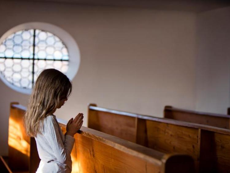 Little girl praying on pew
