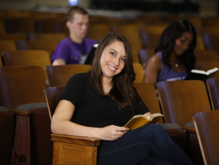 A student sitting in an auditorium reading