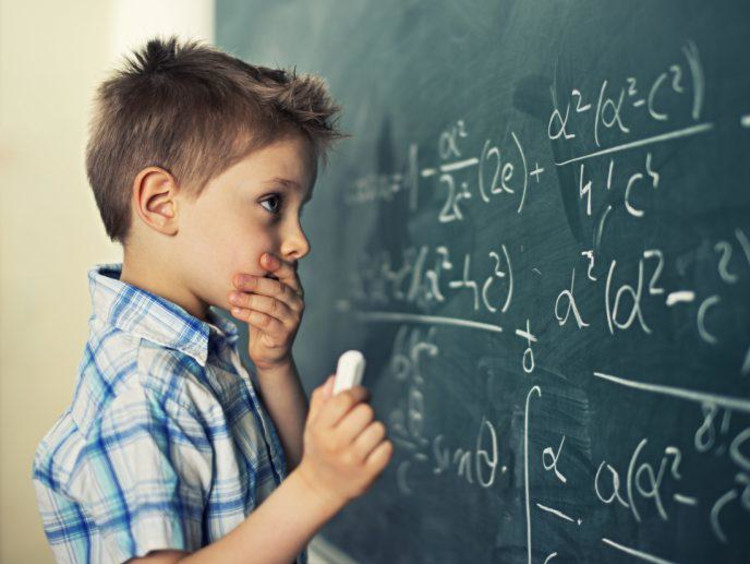 Young student looking at a math problem on a chalkboard
