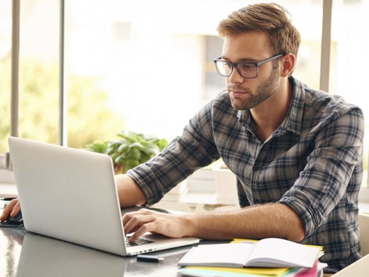 Young male sits at a table working on laptop with coffee and notebooks nearby