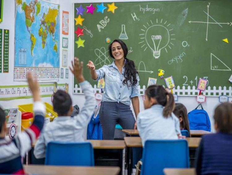 teacher smiling while teaching her students