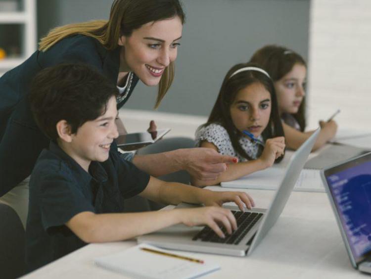 Female teacher helping young children navigate technology