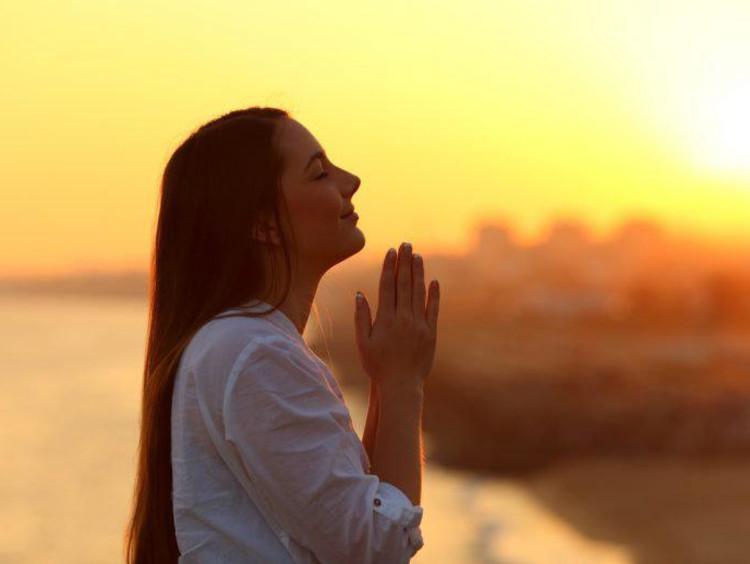 woman praying during sunrise or sunset