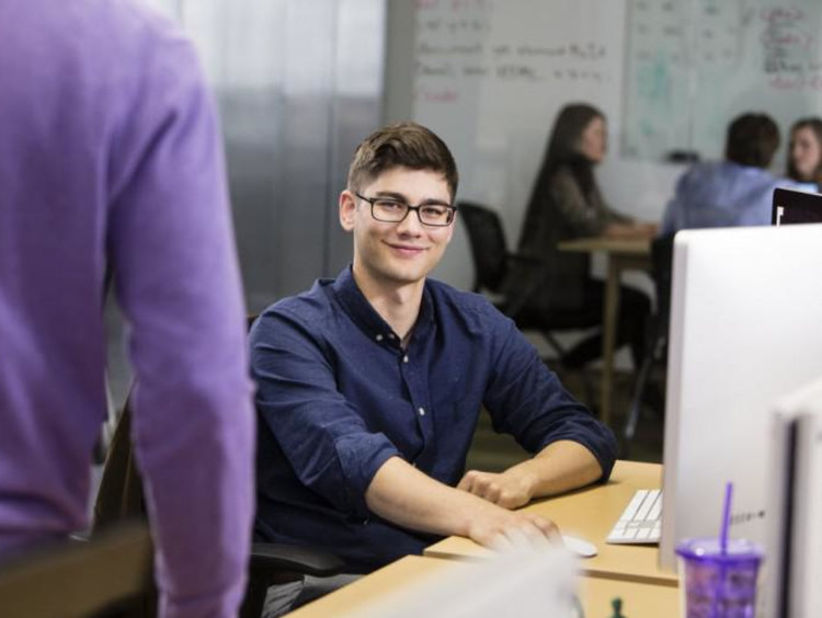 student sitting at a computer smiling