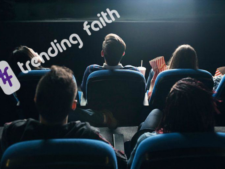 Back view of people seated in a movie theater looking at the front screen