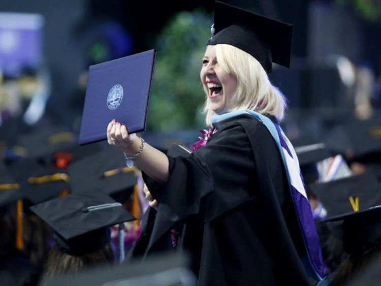 girl excited holding up diploma
