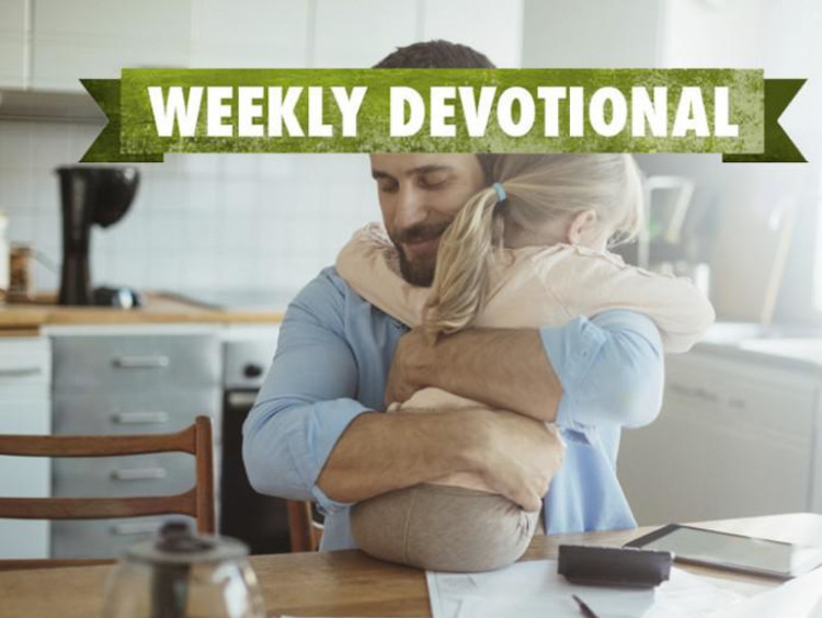 A parent hugging his child under the Weekly Devotional banner
