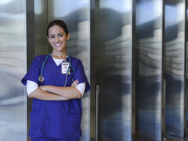 nurse leaning against wall with arms crossed