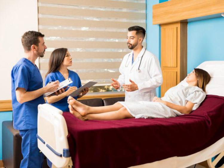 nursing students talking next to a patient