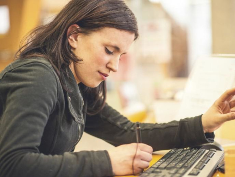 Woman takes notes while pointing at desktop monitor with other hand