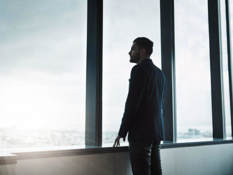 man thinking and looking out of window