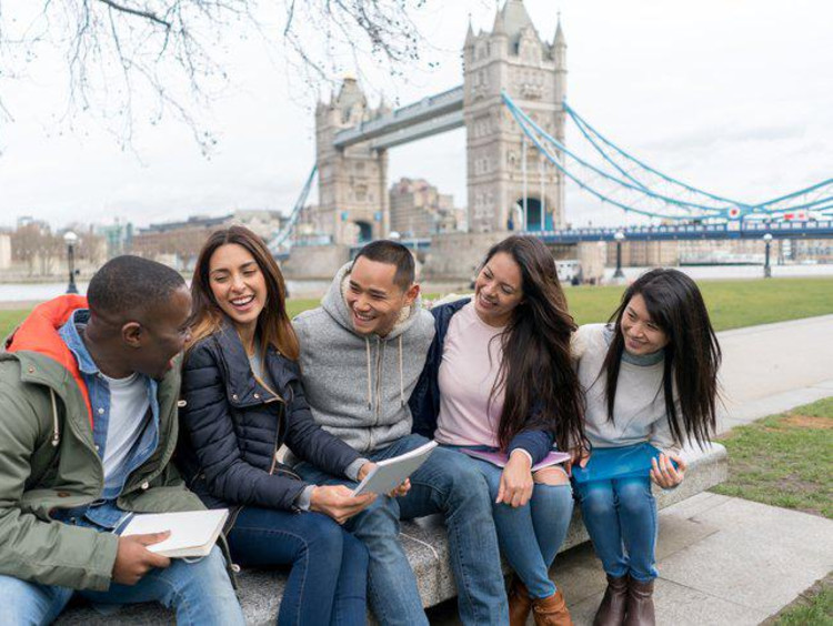 group of students sitting on bench in front of Tower Bridge in London