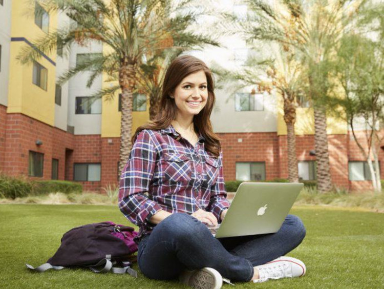 Psychology student sits on lawn in front of GCU dorms