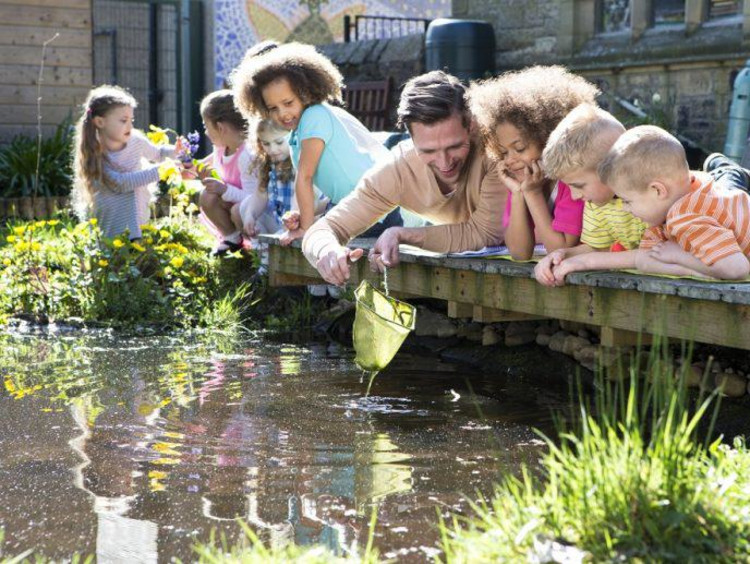 students and teacher outside looking at a pond