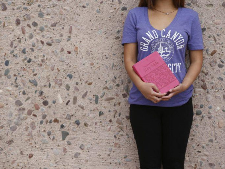 A student in a GCU shirt holding the Bible