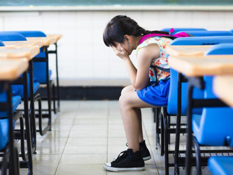 kid sitting in a classroom with head in hands