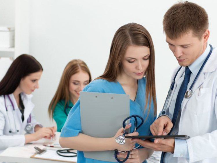 Nurse looking at a screen in doctor's hands