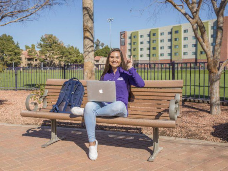 Tatum sitting on a bench on campus