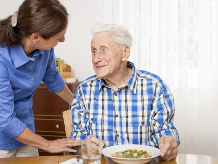 Young adult helps elderly man