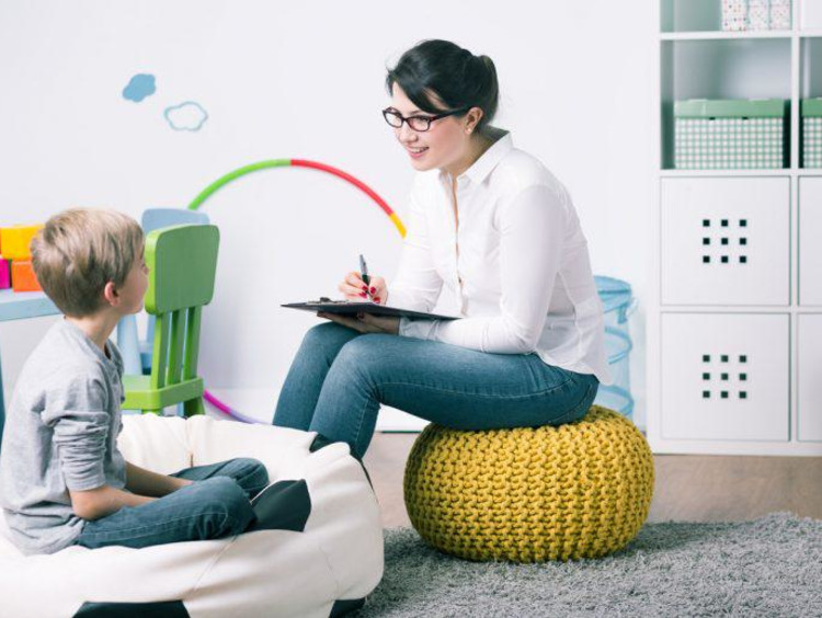A family therapist sits in playroom and asks a little boy questions