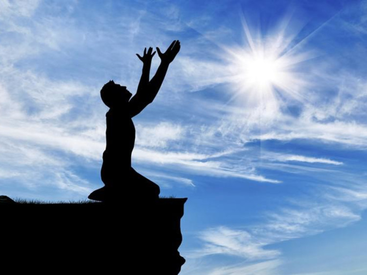 person on knees lifting arms to the sky