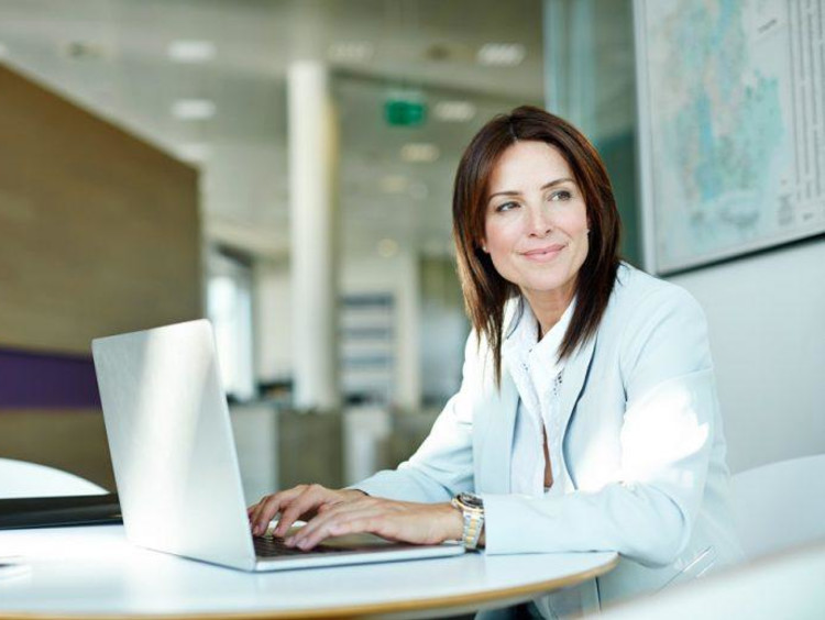 Woman looks away from her laptop screen while working