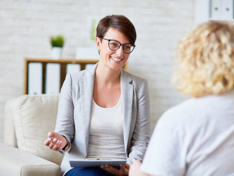 Behavioral health specialist smiles and talks with a patient