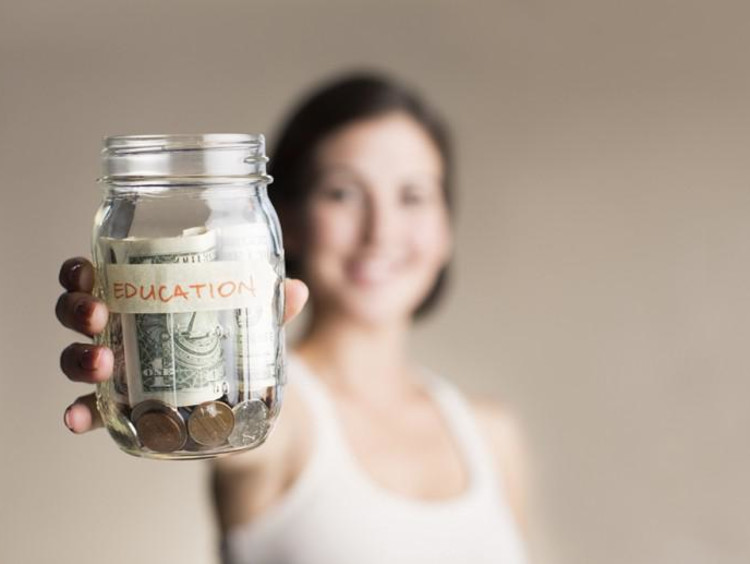 Woman holds out a jar labeled Education with money in it