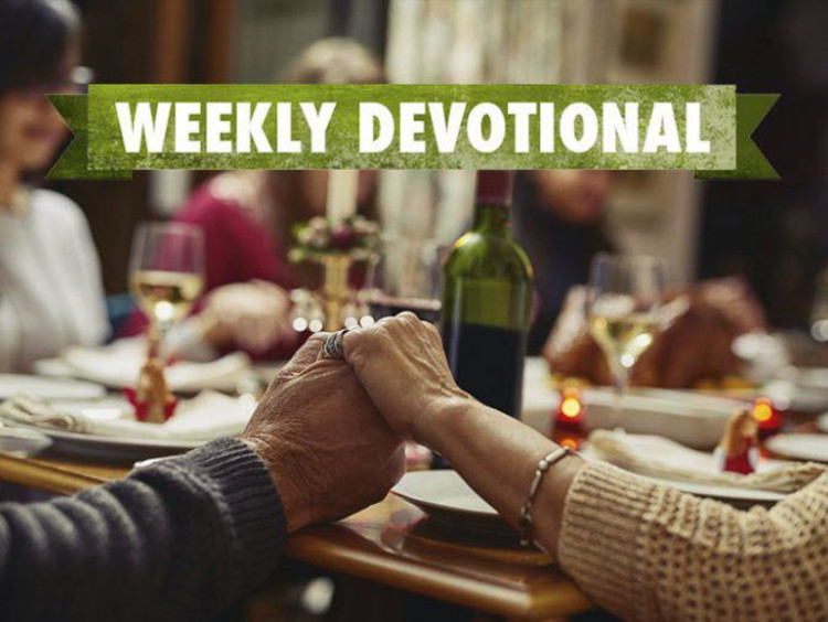Weekly Devotional: Family praying over a dinner