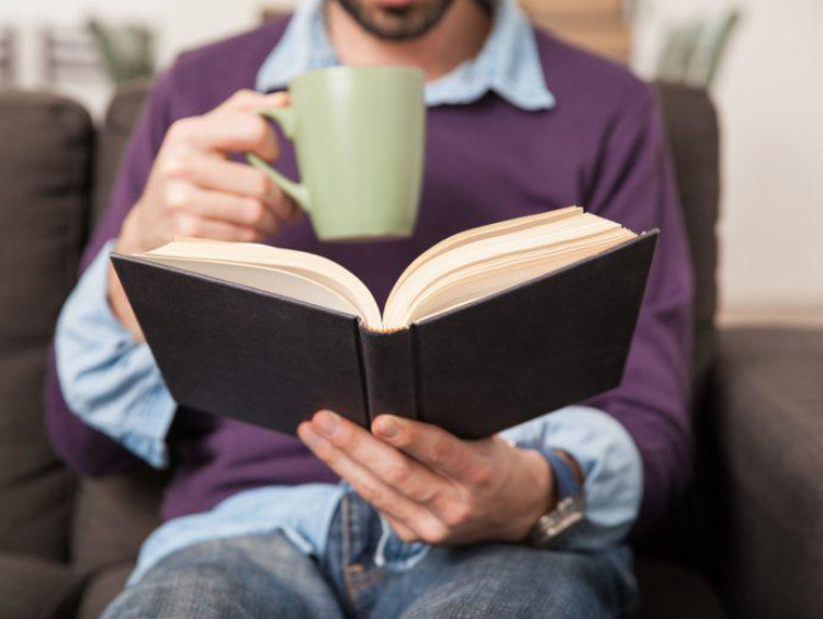A man reading a book with a cup of coffee