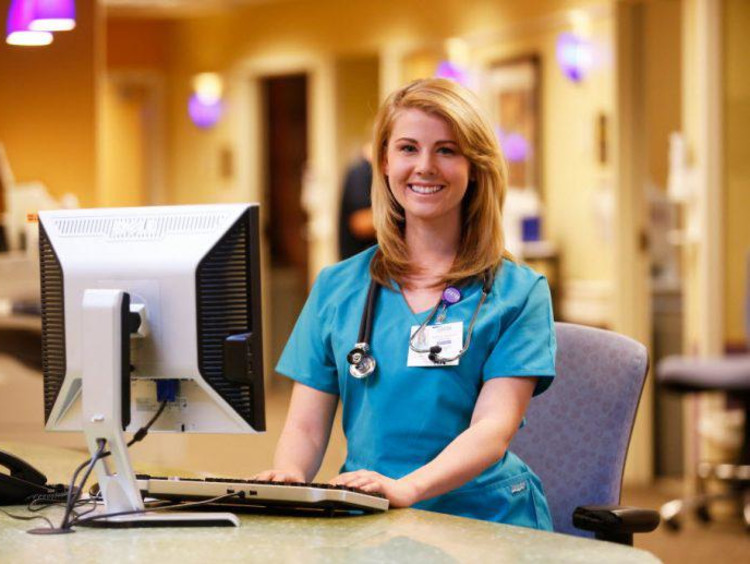 Nurse in scrubs at computer
