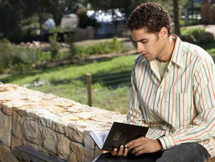 Man sitting while reading the Bible