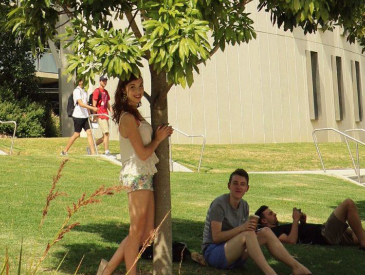 Kaitlyn poses by a tree with another international student