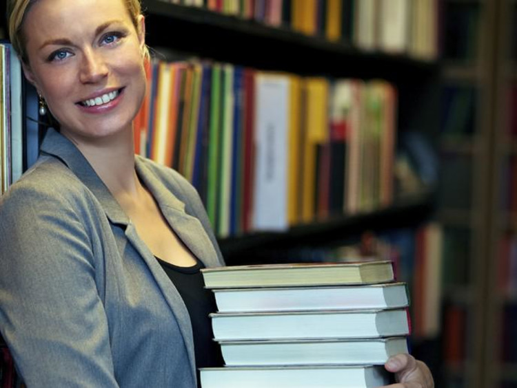 Attractive blonde woman holds stack of books in library