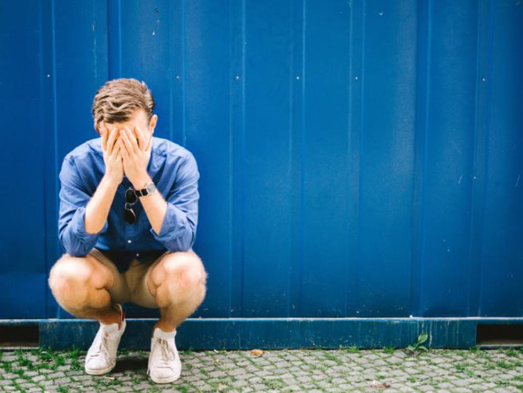 Young man crying in front of a blue curtain