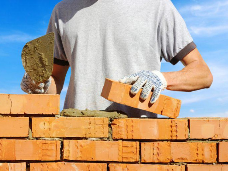 Adult worker laying brick