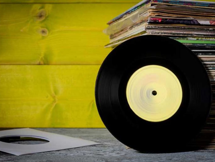 Yellow wall with table of stacked vinyl sleeves and a vinyl leaning against it