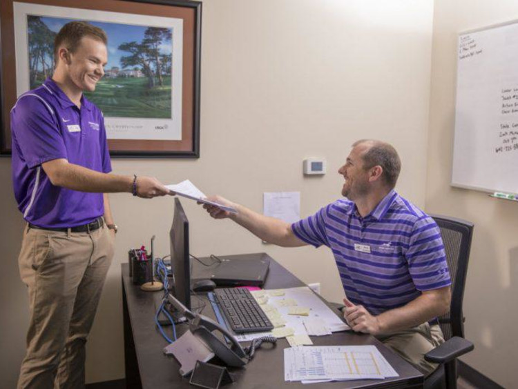 Two GCU golfers interacting in an office