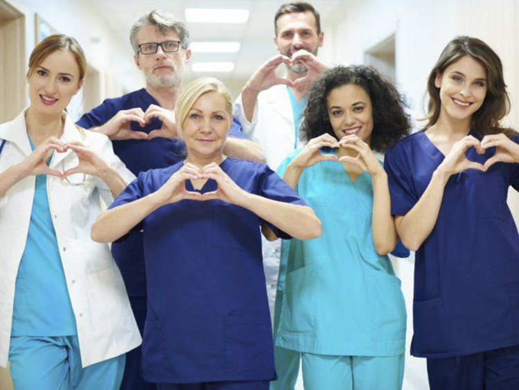 a group of nurses making heart signs
