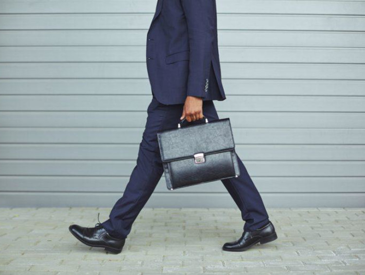 Business man walks on the street with brief case