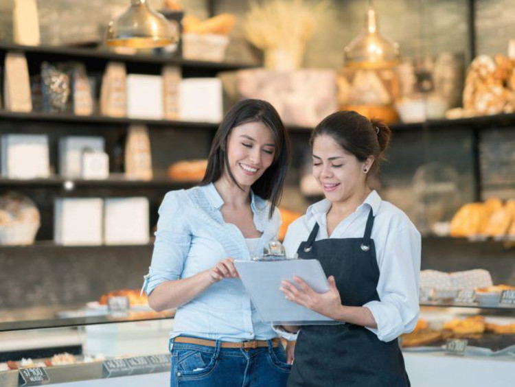 Two businesswomen review a checklist at a chic market shop